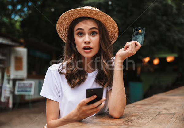 Shocked young girl holding plastic credit card Stock photo © deandrobot