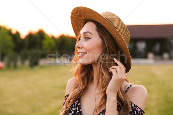 Portrait of amazing young woman 20s wearing straw hat smiling, a Stock photo © deandrobot