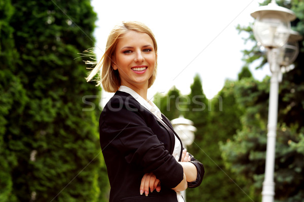 Portrait of a smiling attractive woman with arms folded in park Stock photo © deandrobot