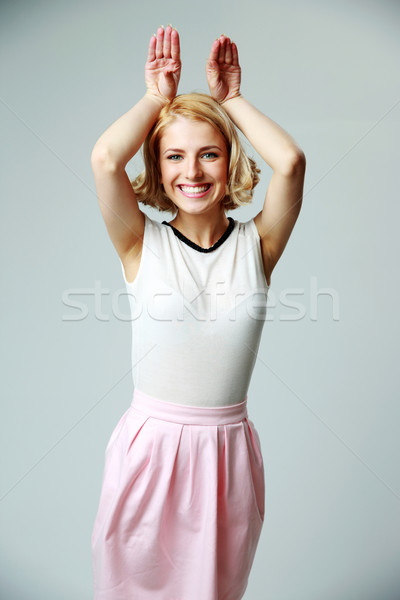 Portrait of a girl raising hands and looking at camera Stock photo © deandrobot