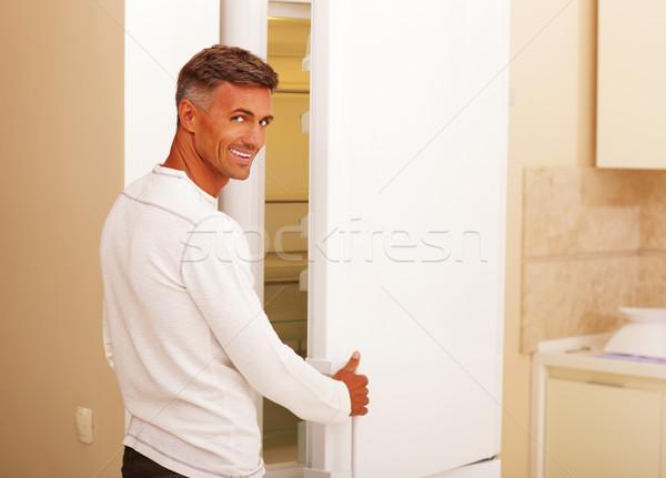 Jóképű boldog férfi nyitás hűtőszekrény otthon Stock fotó © deandrobot