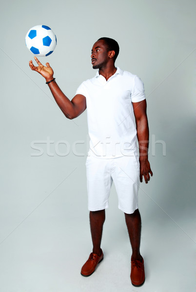 Stock photo: African man spinning a ball on his finger on gray background