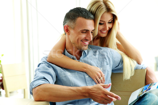 Young couple reading magazine at home Stock photo © deandrobot