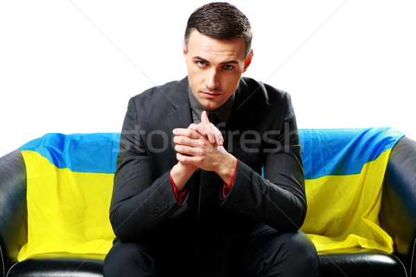 Confident businessman sitting with ukrainian flag on the background Stock photo © deandrobot