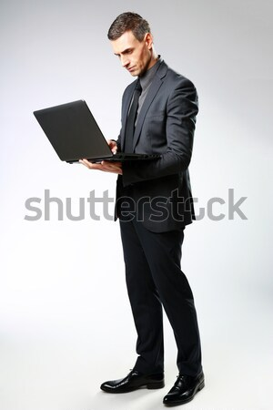 Full-length portrait of a businessman standing and using laptop isolated on a white background Stock photo © deandrobot