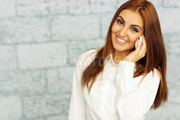 Stock photo: Happy businesswoman talking on phone and sitting at the table