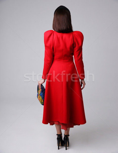 Back view portrait of a woman in red dress on gray background Stock photo © deandrobot