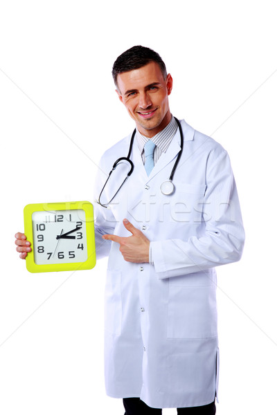 Portrait of a male doctor showing on clock over white background Stock photo © deandrobot