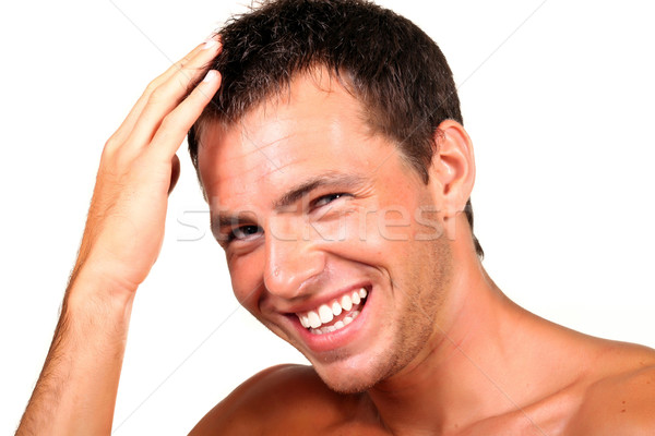 Closeup of a happy young man looking at camera and touching his hair Stock photo © deandrobot