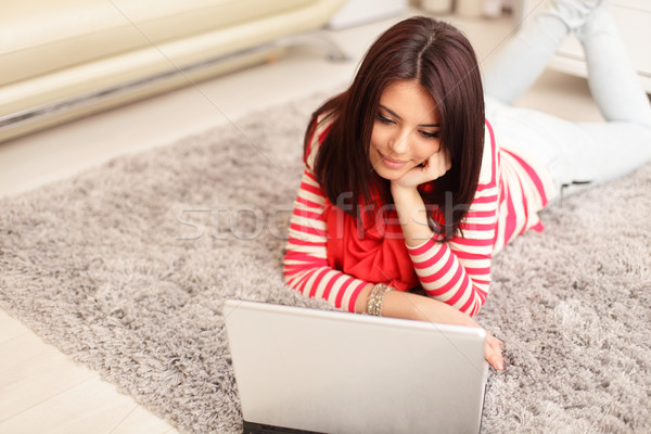 Portrait of dreamy smiling young woman using laptop while lying on floor at home Stock photo © deandrobot