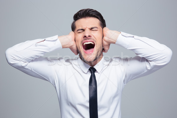 Businessman covering his ears and screaming Stock photo © deandrobot