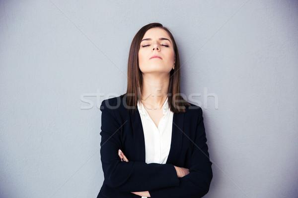 Fiatal üzletasszony csukott szemmel szürke karok összehajtva Stock fotó © deandrobot