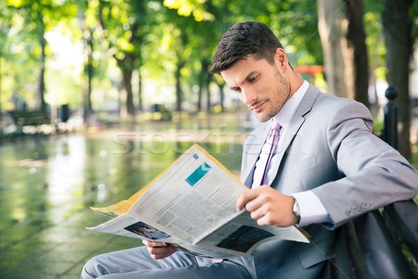 Stock photo: Businessman reading newspaper outdoors