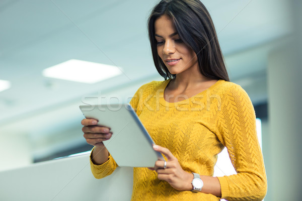 Businesswoman using tablet computer in office  Stock photo © deandrobot
