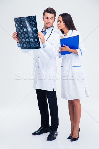 Two medical workers looking at x-ray picture of brain Stock photo © deandrobot