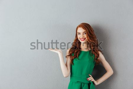 Happy woman pointing finger away Stock photo © deandrobot