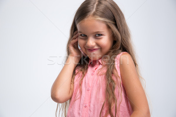 Stock photo: Portrait of a pretty little girl talking on the phone