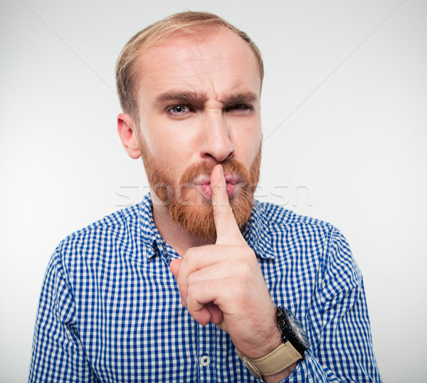 Young casual man showing finger over lips Stock photo © deandrobot