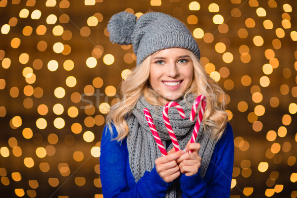 Portrait of a smiling cute woman holding candy cane Stock photo © deandrobot