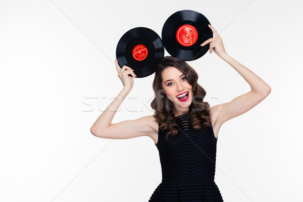 Funny cheerful woman in retro style posing with vinyl records  Stock photo © deandrobot