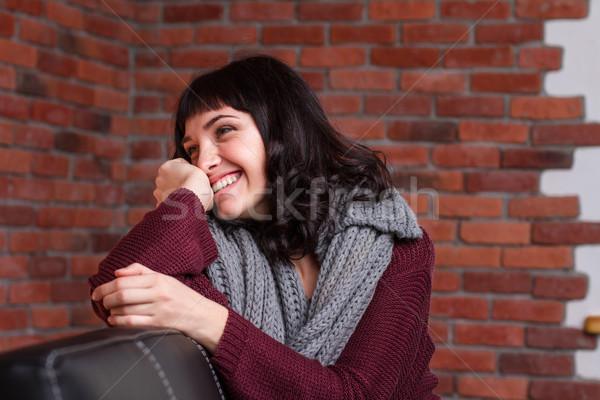 Charming shy young woman sitting on leather sofa and laughing  Stock photo © deandrobot
