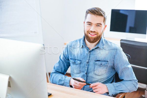 Cheerful handsome designer holding stylus and sitting in office  Stock photo © deandrobot