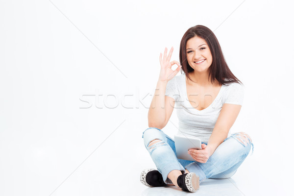 Woman sitting on the floor and showing ok sign Stock photo © deandrobot
