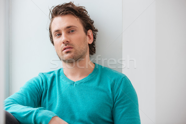 Portrait of handsome relaxed young man in blue jumper  Stock photo © deandrobot