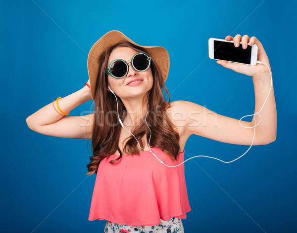 Smiling charming woman listening to music from blank screen smartphone Stock photo © deandrobot