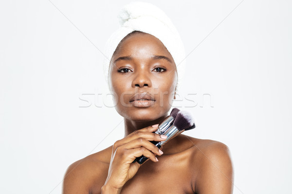 Afro american woman holding makeup brushes Stock photo © deandrobot