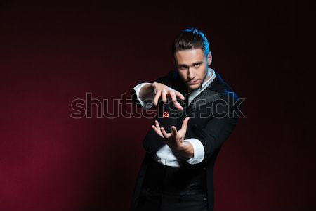 Concentrated young man magician conjuring tricks with red dice Stock photo © deandrobot