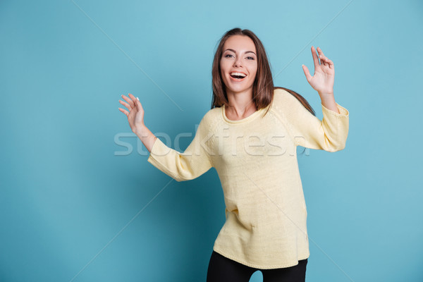 Stock photo: Pretty young smiling girl making fun over blue background
