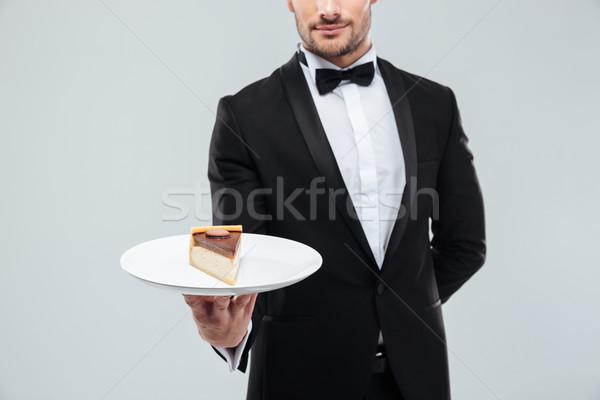 Waiter in tuxedo holding piece of cake on plate Stock photo © deandrobot