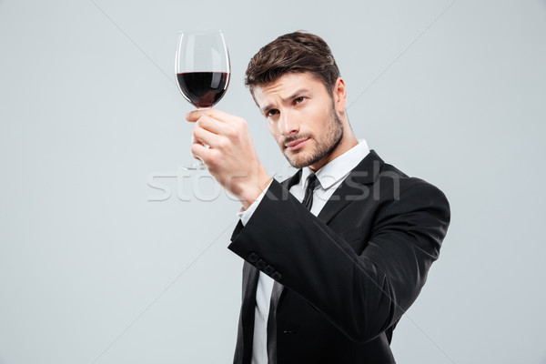 Man sommelier tasting and looking at red wine in glass Stock photo © deandrobot