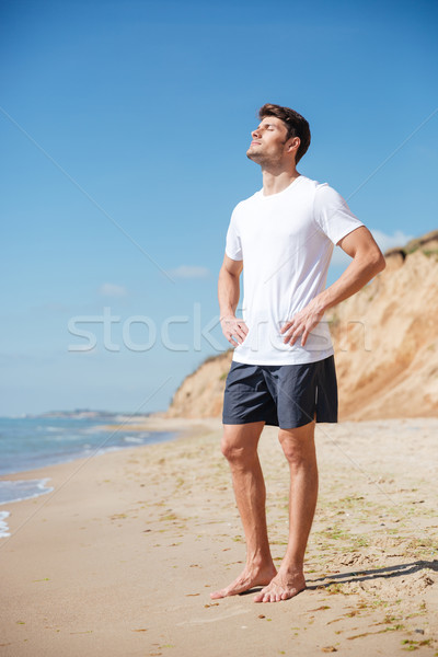 Relaxed man standing barefoot on the beach Stock photo © deandrobot