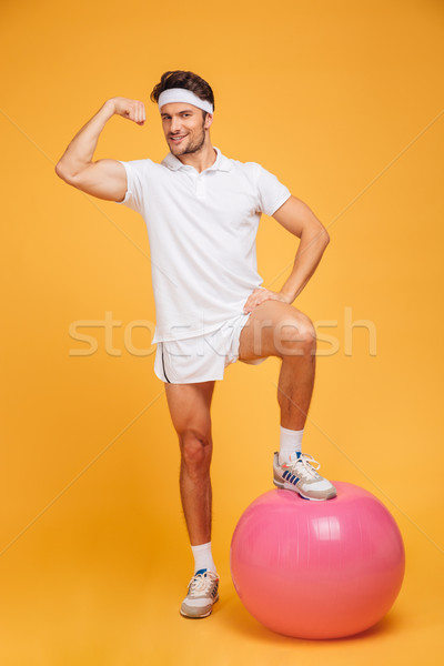 Young handsome sportsman with fitness ball showing biceps Stock photo © deandrobot