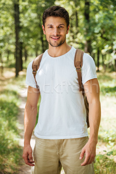 Cheerful young man with backpack standing in forest Stock photo © deandrobot