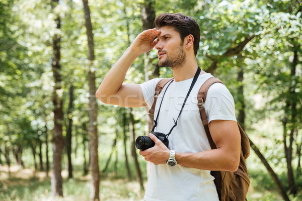Man photographer with modern photo camera looking far away outdoors Stock photo © deandrobot