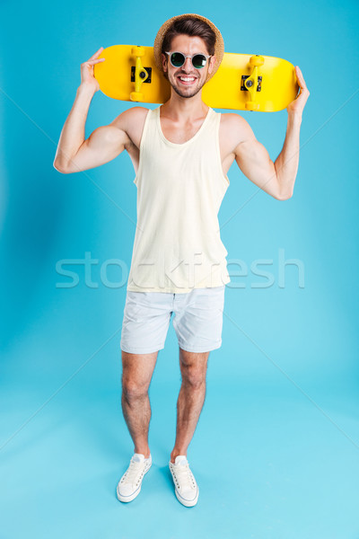 Szczęśliwy młody człowiek szorty hat okulary deskorolka Zdjęcia stock © deandrobot