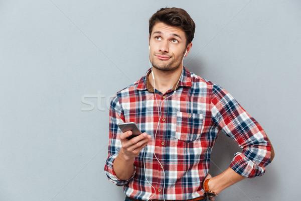 動揺 困惑して 男 イヤホン 音楽を聴く スマートフォン ストックフォト © deandrobot