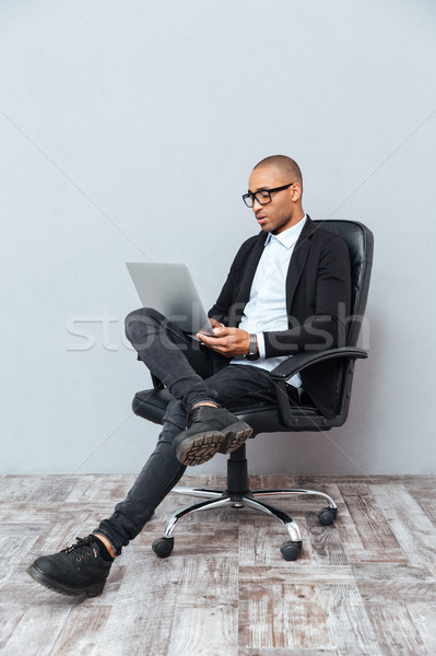 Concentrated young man sitting in office chair and using laptop Stock photo © deandrobot