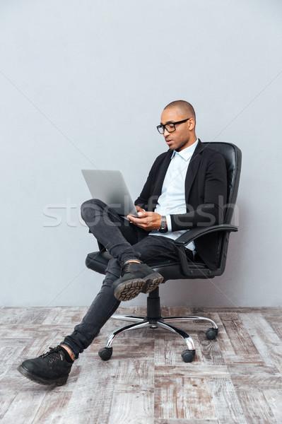 濃縮された 若い男 座って 事務椅子 ラップトップを使用して 眼鏡 ストックフォト © deandrobot