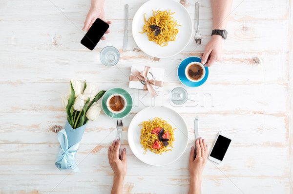 Hands of young couple eating pasta on wooden table Stock photo © deandrobot