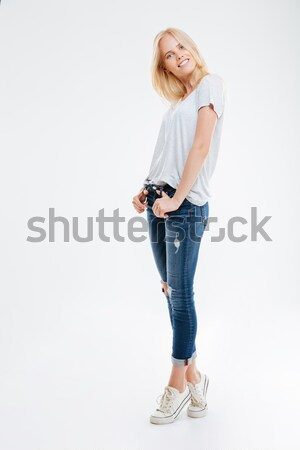 Smiling young woman standing with hands in pockets on tiptoe Stock photo © deandrobot