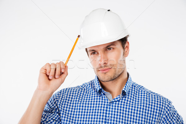 Thoughtful young man builder in building helmet with pencil thinking Stock photo © deandrobot