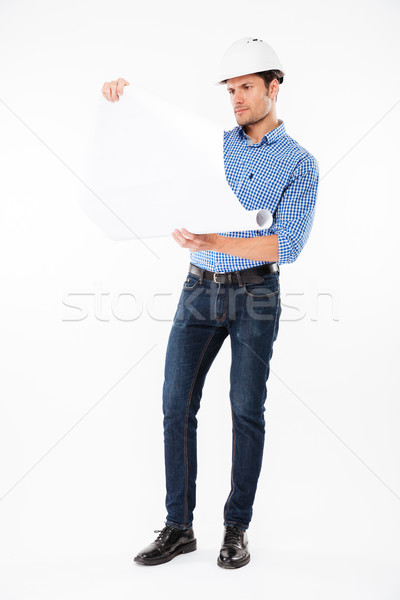 Man architect in hard hat holding and looking at blueprint Stock photo © deandrobot