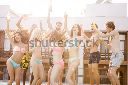 Group of friends having fun at swimming pool outdoors Stock photo © deandrobot