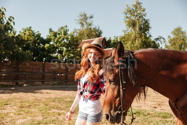 Cheerful young woman cowgirl walking wit her horse on ranch Stock photo © deandrobot