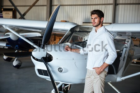 Man standing with arms crossed and smiling near small plane Stock photo © deandrobot