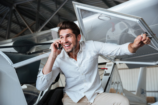 Smiling man talking on cell phone in small aircraft Stock photo © deandrobot